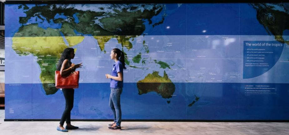 Two students chatting in front of a map of the Tropics