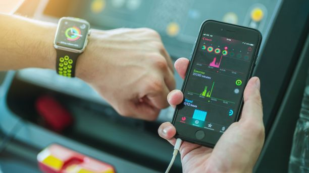 Person compares data on smartphone and smartwatch