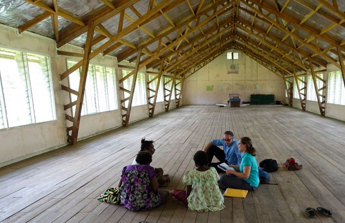 PNG locals and researchers sit on the floor of a building to talk