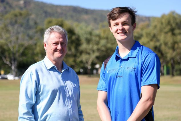 Professor Chris Cocklin and Jake Doran pose for a photo taken outside with Mount Stuart in the background