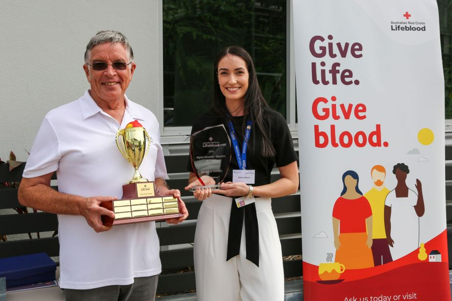 Bill Tweddell and Bianca Johnson hold trophies and stand next to a blood donation promotional banner