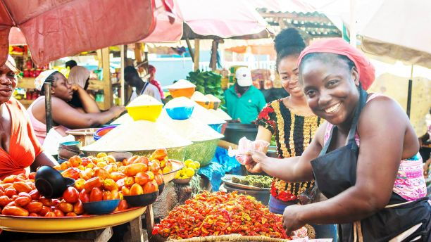African woman sells vegetables in the marketplace