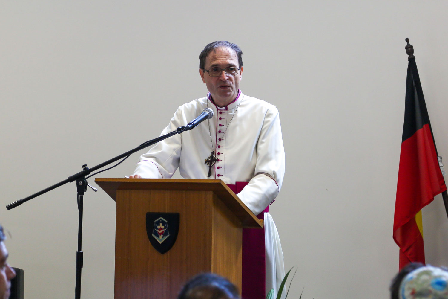 a man at a lectern in white religious robes