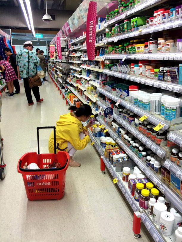 A Chinese tourist looking at vitamins in an Australian supermarket.