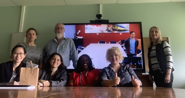An Assortment of 7 people standing infront of a Screen showing a video call with an additional person, all posing to the camera.