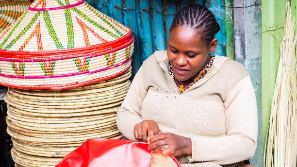 African woman making baskets to sell