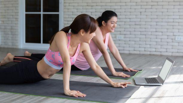 Women exercising watching laptop