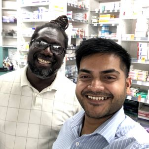 Two pharmacists smiling in shop