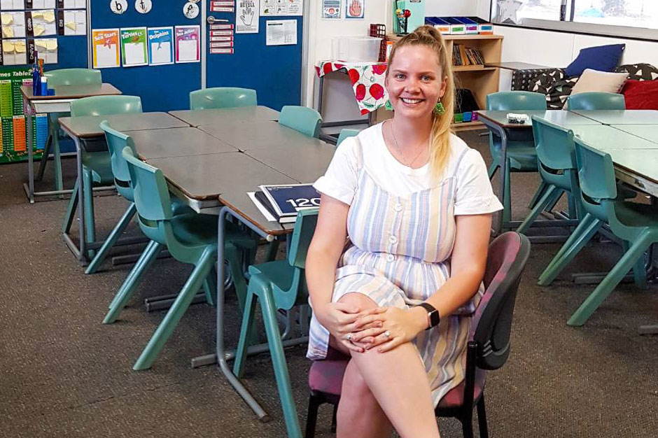 Tia sitting on a chair in a primary school classroom