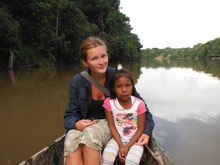 Researcher posing with child on a boat.
