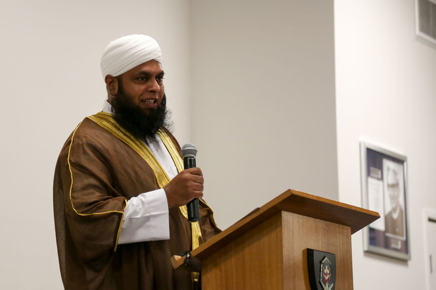 Imam Abdullah Salik wears prayer robes and holds a microphone while standing at a lectern
