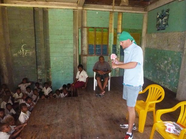 Student Mathew Robertson demonstrating dental hygiene to school children