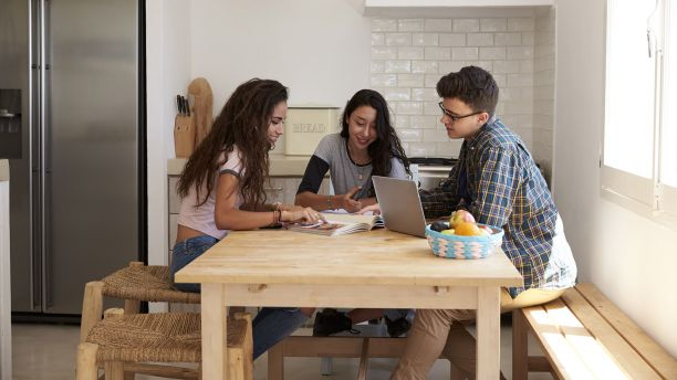 Three teenagers sharing a laptop