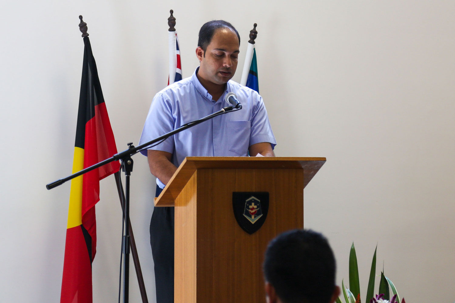 a man stands at a lectern, The Australian, Aboriginal, and Torres Strait Islander flags behind, looking down at his notes
