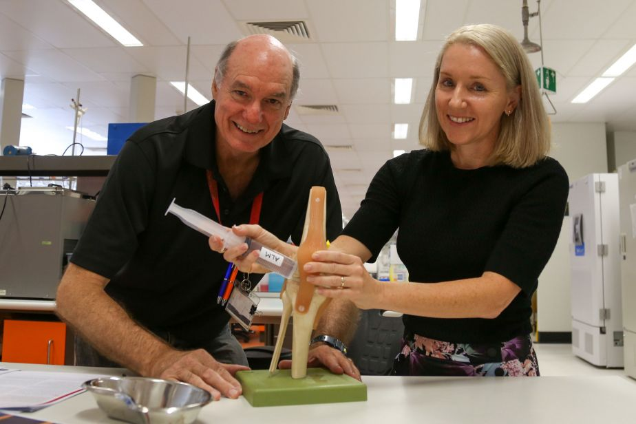 A male and a female pose with a plastic model of a knee joint