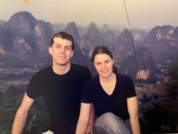 Siblings Richard and Sarah sitting next to each other with mountains in China in background