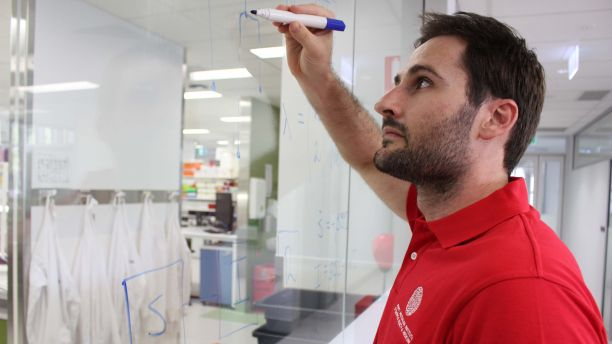 Michael Meehan writing on clear glass with a whiteboard marker with a laboratory in the background