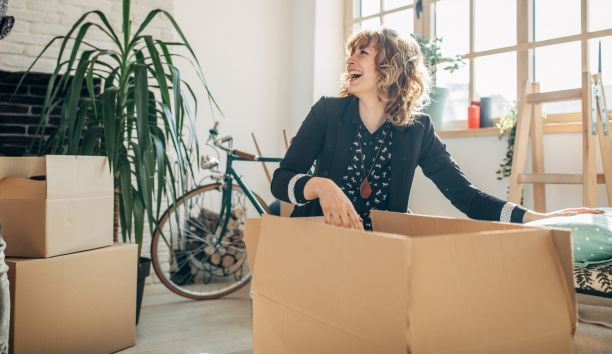 A smiling woman is laughing while reaching into a packing box and is surrounded by other packing boxes.