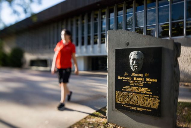 A student wearing a red shirt is out of focus as she walks past the Eddie Koiki Mabo commemorative plaque