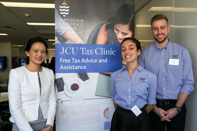 A staff member and two students stand next to a banner advertising the Tax Clinic