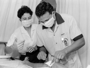 A nursing student being supervised by a clinical educator as he proceeds with a wound dressing
