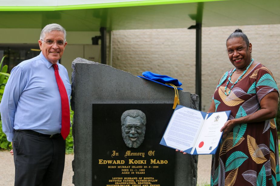 Chancellor Bill Tweddell and Gail Mabo stand on either side of a plaque commemorating Eddie. A PhD bonnet is on top of the plaque and Gail holds open a blue folder showing the testator