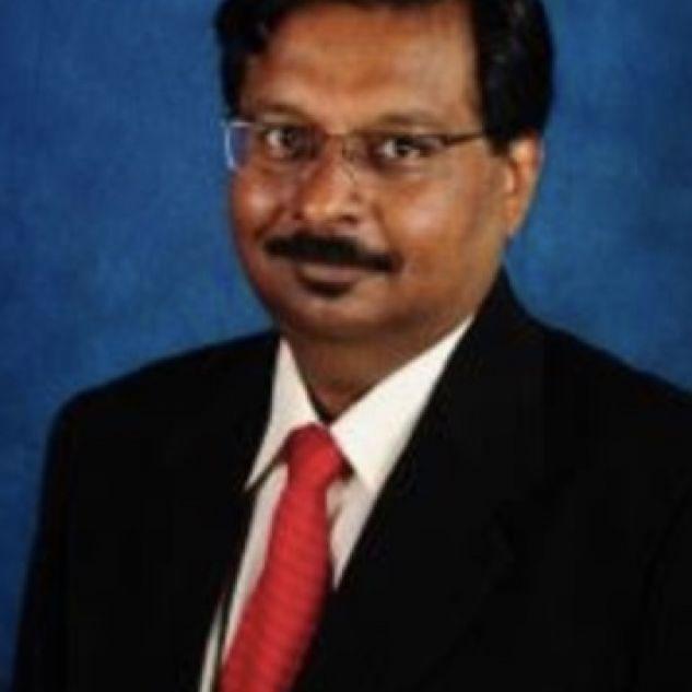 Kunwarjit Sangla wearing a black suit with a red tie