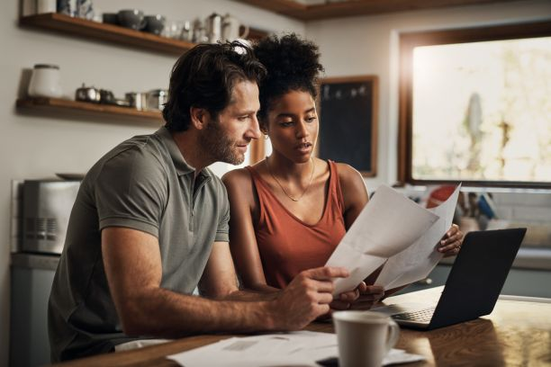 A man and a woman sit at a kitchen table with a laptop while each holding up pieces of paper and looking at them together.