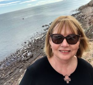 Dr Kerrie Mackey-Smith, a JCU Education lecturer, is smiling and wearing sunglasses with the beach in the background.