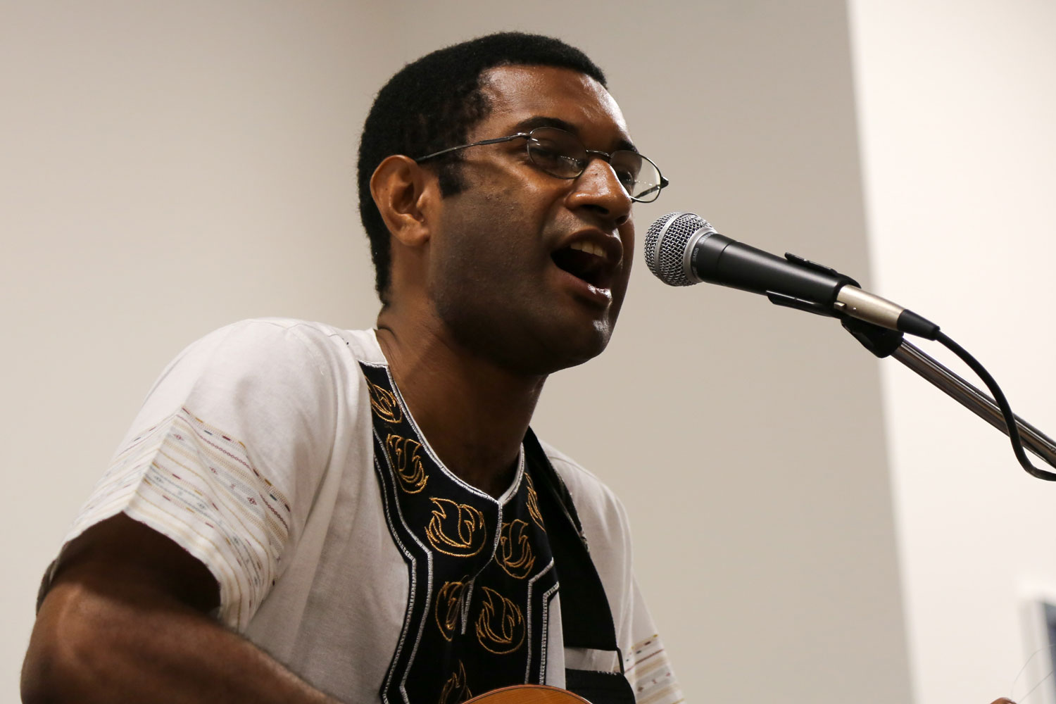 A man sings into a microphone while playing the guitar