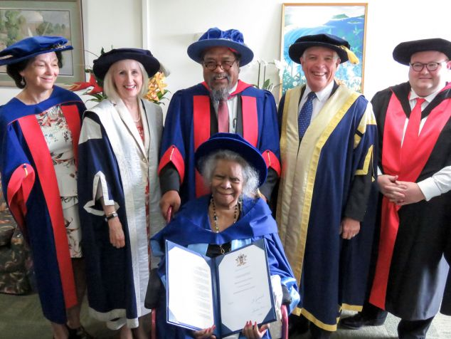 JCU academics in robes stand Behind Bonita Mabo, who is holding her honorary doctorate and wearing academic dress