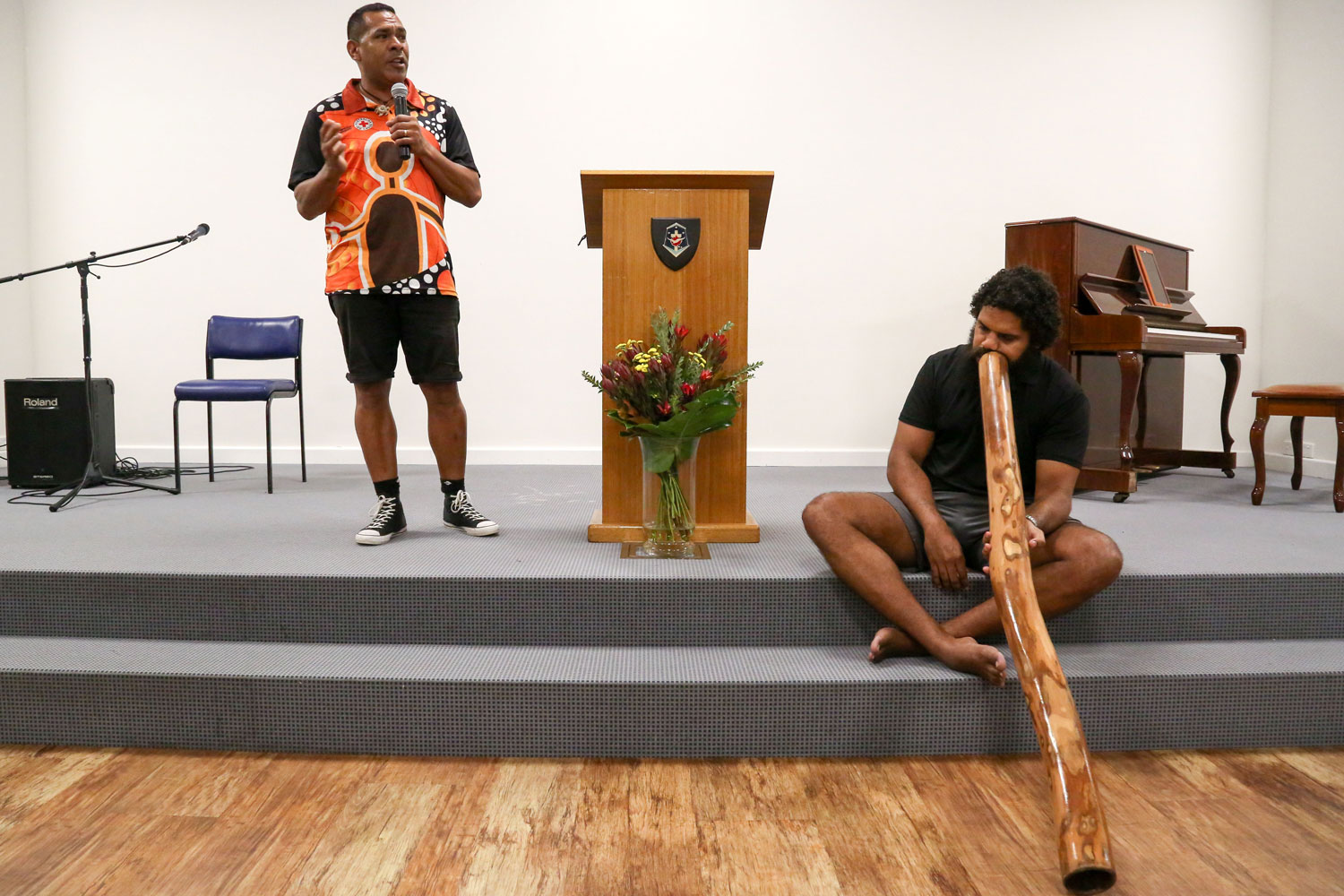 Welcome to country from Sam Savage standing on stage, as William Mabo sits playing a didgeridoo