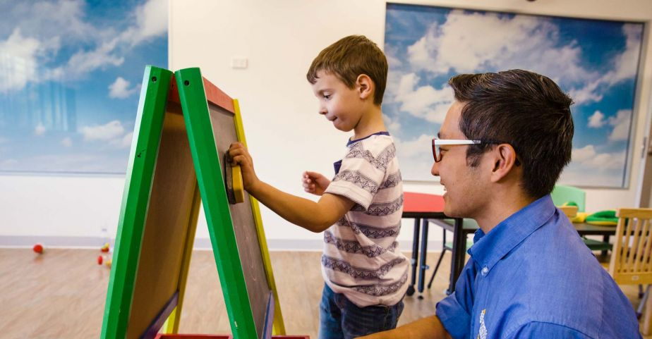 Early childhood educator assisting student who is writing on a chalk-board easel