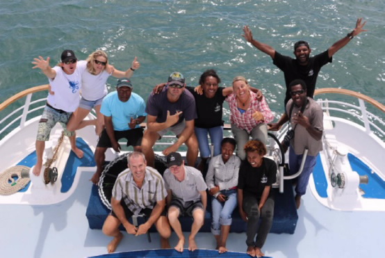 A top down view of the survey team on the boat, with blue water in the background.