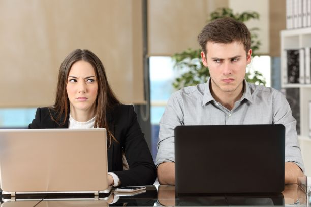 Man and woman look angrily at each other while work at laptops