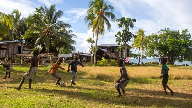 Group of kids playing soccer in Chea Village, Solomon Islands