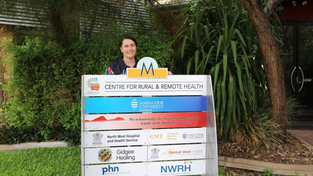 Nurse Emily Hapgood standing next to the Mt Isa Centre for Rural and Remote Health sign
