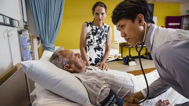 Nurse practitioner supervises a medical trainee with patient