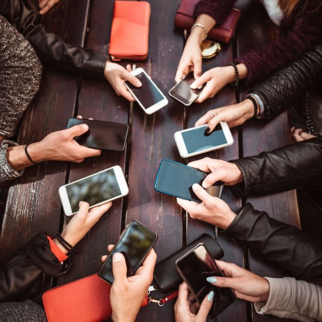 Seven people's hands gathered around a table each holding phones.