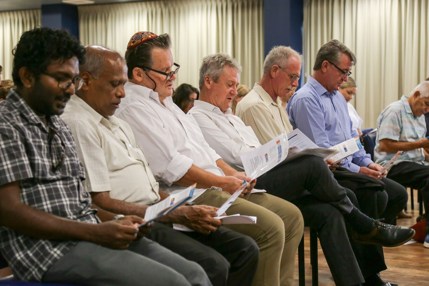 Six men sitting down reading from the program