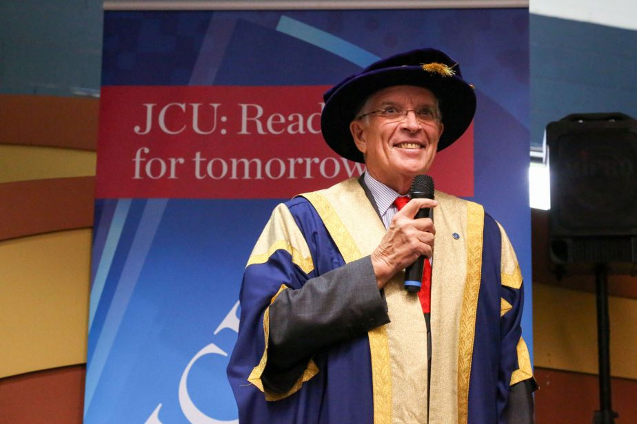 Bill Tweddell smiles while speaking into a microphone, wearing his chancellor regalia, in front of a JCU banner