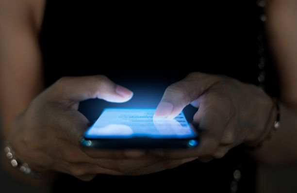 Close up of one person's hands holding a phone that is lighting up the dark around them.