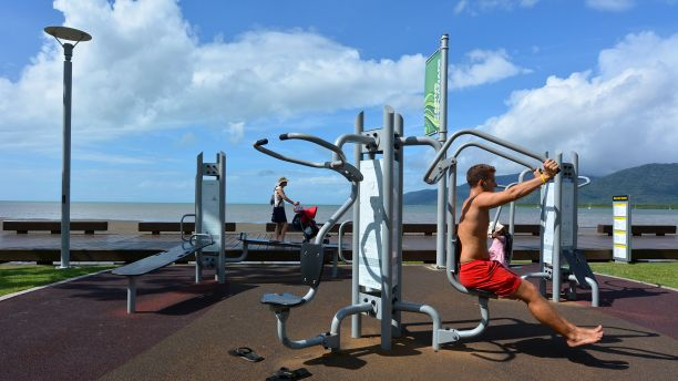 Man exercising on outdoor gym equipment