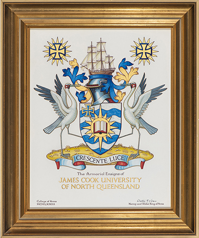 The JCU Coat of Arms featuring a blue and gold shield, a ship, two Brolgas, and the motto crescent luce