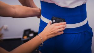Sports Scientist attaching a GPS device to an athlete's back
