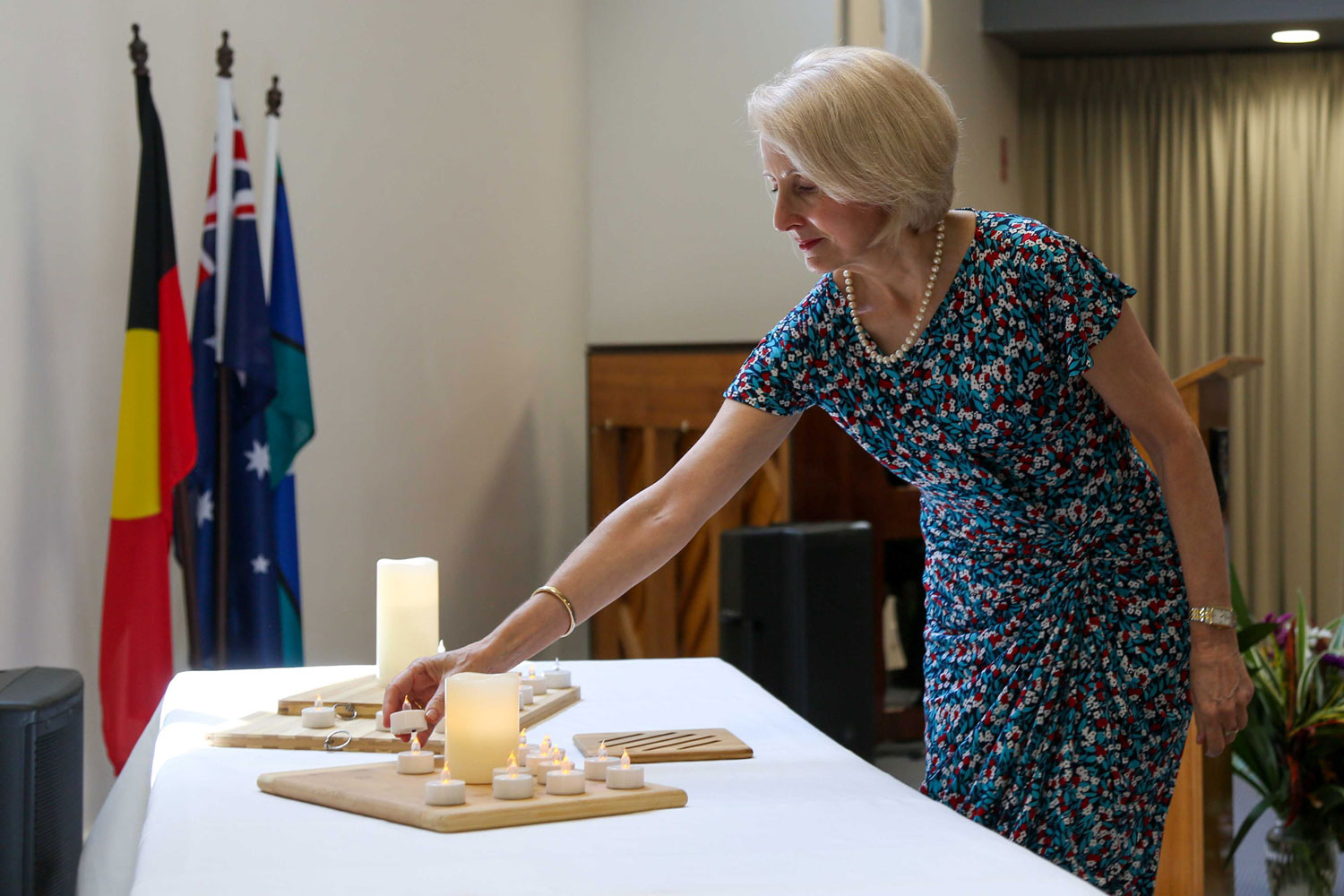 a woman reaches to place an electric candle on a table among others