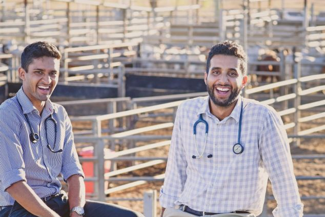 Sixth year JCU medical students Tarren Zimsen and Steven Bajwa sitting on a stock fence in Charters Towers.