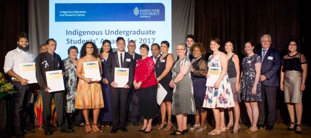 Award winners and JCU staff members pose on stage as a group