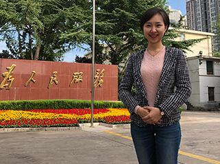 Huan Lu (Ella), from China, who studied her PhD in Tourism Management with JCU, standing in front of a sign with Chinese writing on it