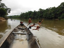 Children jumping into river from boat.